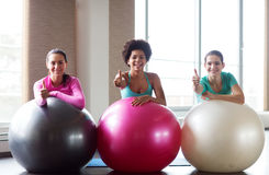 Group of smiling women with exercise balls in gym. Fitness, sport, training and lifestyle concept - group of smiling women with exercise balls in gym Royalty Free Stock Image