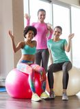 Group of smiling women with exercise balls in gym Stock Photo