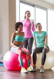 Group of smiling women with exercise balls in gym. Fitness, sport, training and lifestyle concept - group of smiling women with exercise balls in gym Royalty Free Stock Photos