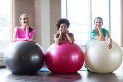 Group of smiling women with exercise balls in gym. Fitness, sport, training and lifestyle concept - group of smiling women with exercise balls in gym Royalty Free Stock Images