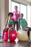 Group of smiling women with exercise balls in gym. Fitness, sport, training and lifestyle concept - group of smiling women with exercise balls in gym Stock Photography