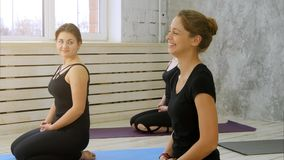 Group of smiling women listen to a yoga instructor in fitness studio stock photography