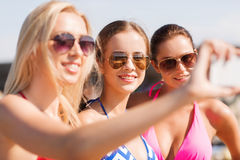 Group of smiling women making selfie on beach Stock Photos
