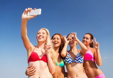 Group of smiling women making selfie on beach Royalty Free Stock Image
