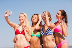 Group of smiling women making selfie on beach Stock Images