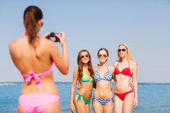 Group of smiling women photographing on beach Stock Photography
