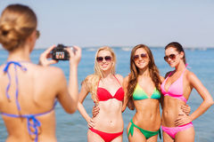 Group of smiling women photographing on beach. Summer vacation, gesture, travel and people concept - group of smiling young women photographing by camera and royalty free stock photo