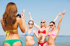 Group of smiling women photographing on beach Stock Photos