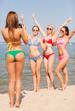 Group of smiling women photographing on beach. Summer vacation, holidays, gesture and people concept - group of smiling women photographing by camera and showing Royalty Free Stock Images