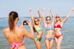 Group of smiling women photographing on beach Stock Photo