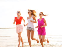 Group of smiling women running on beach Stock Photo