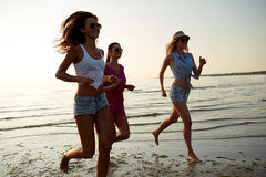 Group of smiling women running on beach. Summer vacation, holidays, travel and people concept - group of smiling young women in sunglasses and casual clothes stock images