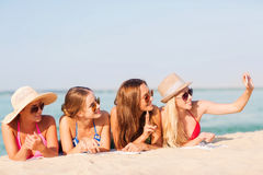 Group of smiling women with smartphone on beach Stock Photography