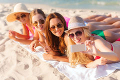 Group of smiling women with smartphone on beach Stock Photos
