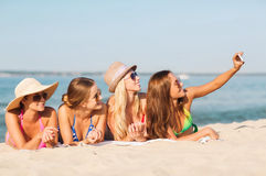 Group of smiling women with smartphone on beach. Summer vacation, travel, technology and people concept - group of smiling women in sunglasses and hats making stock images