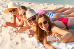 Group of smiling women with smartphone on beach Royalty Free Stock Photo