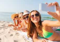 Group of smiling women with smartphone on beach. Summer vacation, travel, technology and people concept - group of smiling women in sunglasses making selfie with royalty free stock images