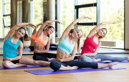Group of smiling women stretching in gym Stock Photography