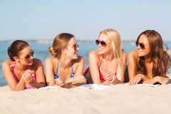 Group of smiling women in sunglasses on beach. Summer vacation, holidays, travel and people concept - group of smiling young women in sunglasses lying on beach Royalty Free Stock Image