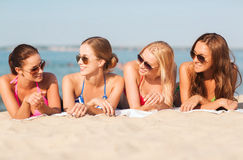 Group of smiling women in sunglasses on beach. Summer vacation, holidays, travel and people concept - group of smiling young women in sunglasses lying on beach Royalty Free Stock Photo