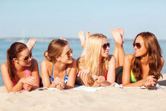 Group of smiling women in sunglasses on beach. Summer vacation, holidays, travel and people concept - group of smiling young women in sunglasses lying on beach Stock Images