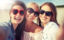 Group of smiling women taking selfie on beach. Summer vacation, holidays, travel and people concept- group of smiling young women taking selfie on beach stock image
