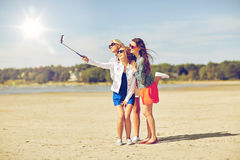 Group of smiling women taking selfie on beach. Summer vacation, holidays, travel, technology and people concept- group of smiling young women taking picture with stock images