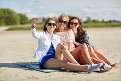 Group of smiling women taking selfie on beach Stock Photos