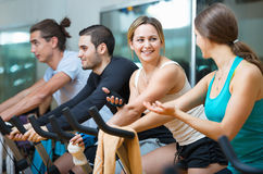 Group smiling  working out of cycling in  fitness club. Group smiling  working out of cycling in modern fitness club Royalty Free Stock Photo