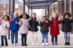 A group of smiling young multi-ethnic school kids wearing coats and carrying schoolbags standing in a row in walkway outside their. Infant school waving to royalty free stock photo