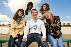 Group of smiling young people on a bench. Five teenagers sitting on a bench at the seaside Stock Photo