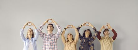 Group of smiling young people doing symbolic heart shape gesture on gray background