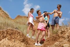A group of smiling young people gives five each other on a top of a valley on a natural blurred background. Stock Images