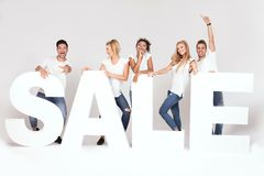 Group of smiling young people posing with sale letters. royalty free stock image