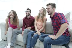 Group of smiling young people sitting on the couch Royalty Free Stock Photo