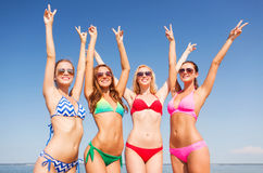 Group of smiling young women on beach. Summer vacation, holidays, gesture, travel and people concept - group of smiling young women showing peace or victory sign royalty free stock photos