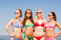 Group of smiling young women on beach. Summer vacation, holidays, travel and people concept - group of smiling young women on beach stock images
