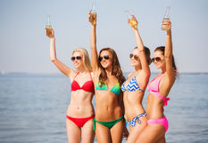 Group of smiling young women drinking on beach royalty free stock photography