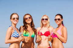 Group of smiling young women drinking on beach Stock Photo