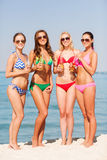 Group of smiling young women drinking on beach Royalty Free Stock Image