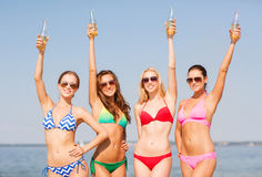 Group of smiling young women drinking on beach. Summer vacation, holidays, travel and people concept - group of smiling young women sunbathing and drinking on royalty free stock images