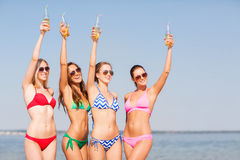 Group of smiling young women drinking on beach Royalty Free Stock Photo