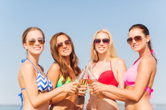 Group of smiling young women drinking on beach Stock Photography