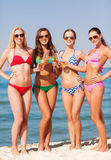 Group of smiling young women drinking on beach. Summer vacation, holidays, travel and people concept - group of smiling young women sunbathing and drinking on royalty free stock photos