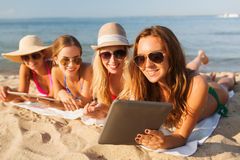 Group of smiling young women with tablets on beach Stock Images