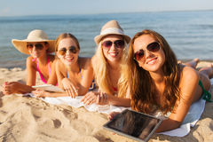 Group of smiling young women with tablets on beach Stock Image