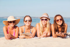 Group of smiling young women with tablets on beach. Summer vacation, travel, technology and people concept - group of smiling women in sunglasses with tablet pc Stock Photo