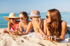 Group of smiling young women with tablets on beach. Summer vacation, travel, technology and people concept - group of smiling women in sunglasses with tablet pc Stock Photography