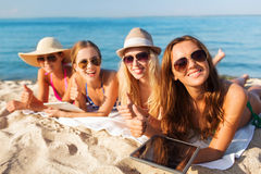 Group of smiling young women with tablets on beach. Summer vacation, travel, technology and people concept - group of smiling women in sunglasses with tablet pc stock photos