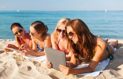 Group of smiling young women with tablets on beach. Summer vacation, travel, technology and people concept - group of smiling women in sunglasses with tablet pc royalty free stock images